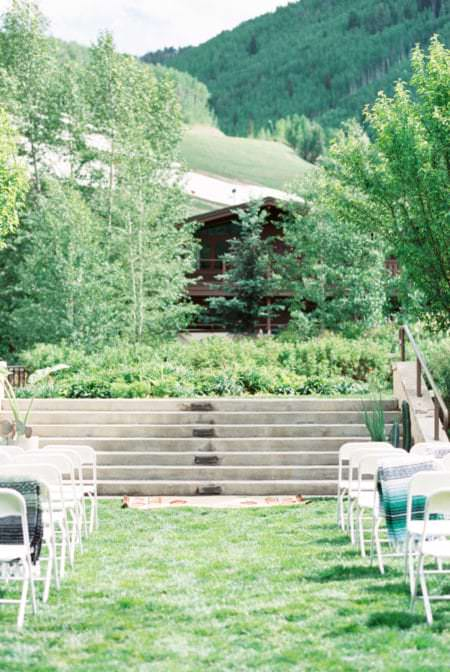 Mountain wedding ceremony set up with white chairs, blankets and a mountainous view.