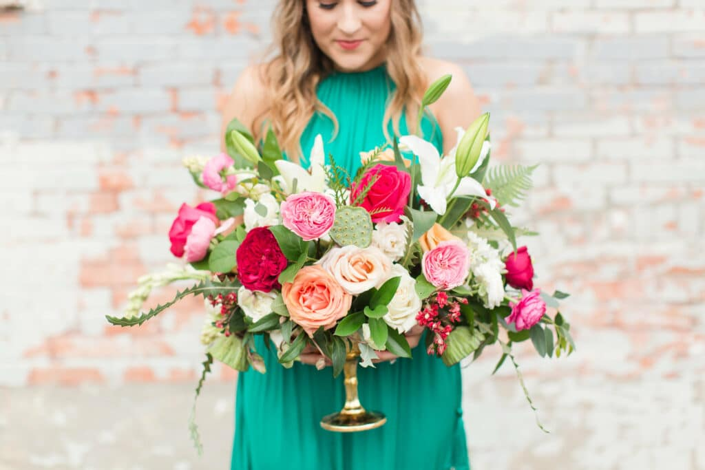 Girl in green dress holding brightly colored floral bouquet