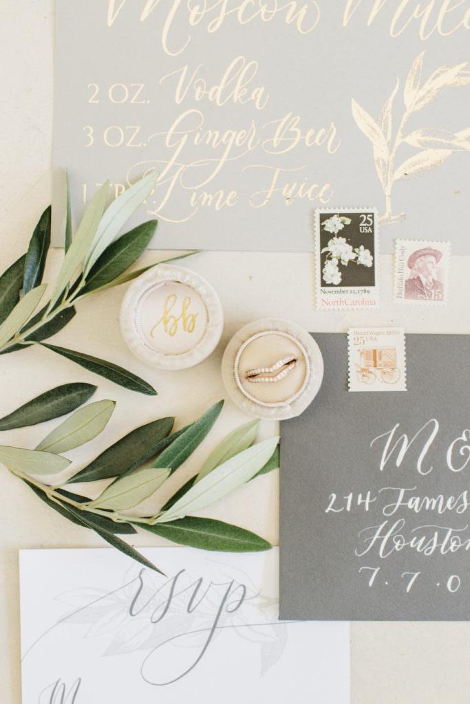 Wedding flat lay of invites, cocktail menu, wedding ring, leaves