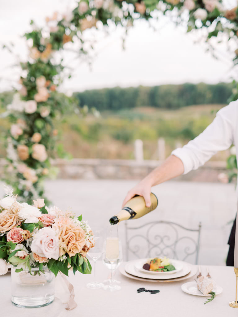 Wedding table set-up with waiter pouring wine into a glass