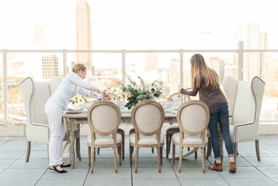 Wedding planners arranging a table at a styled shoot