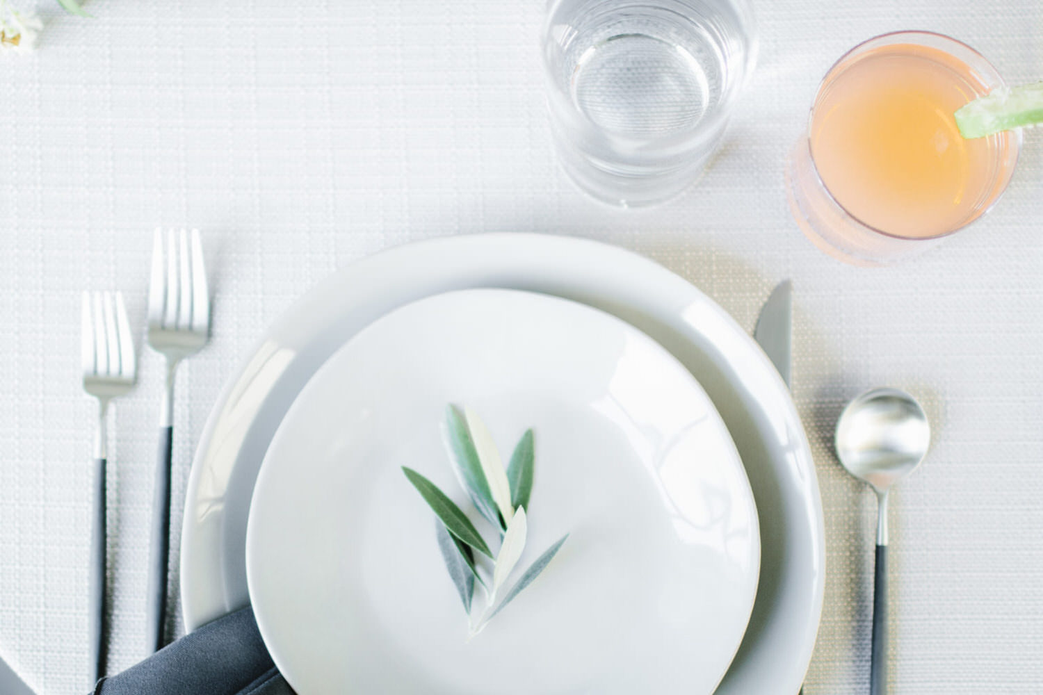 Table setting with white plates and a sprig of a herb, glass of water, silver cutlery