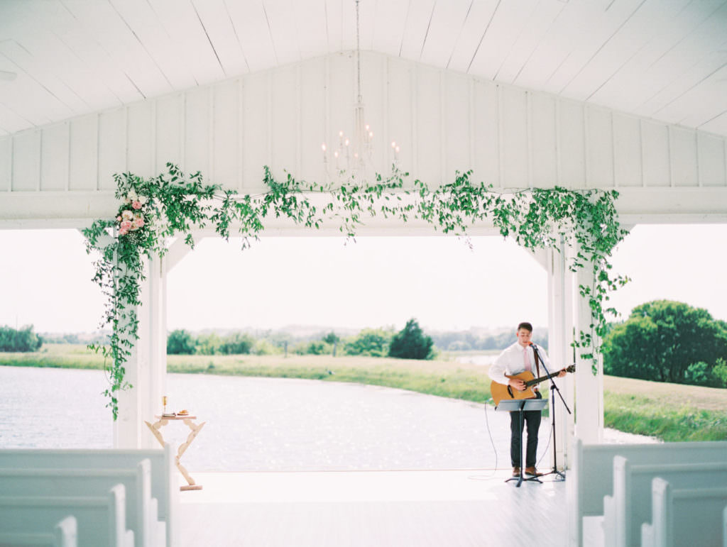 Musician with guitar at wedding ceremony set up, white chairs and green floral decor