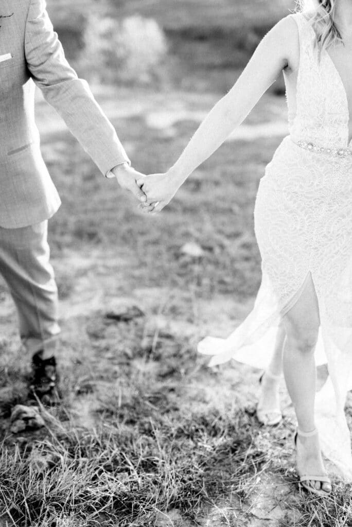 Black and white image of bride and groom walking whilst holding hands