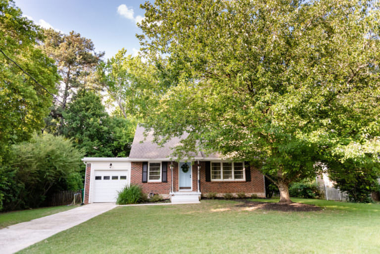 Cute house with pale blue front door, shutters, white garage door, lawn, trees