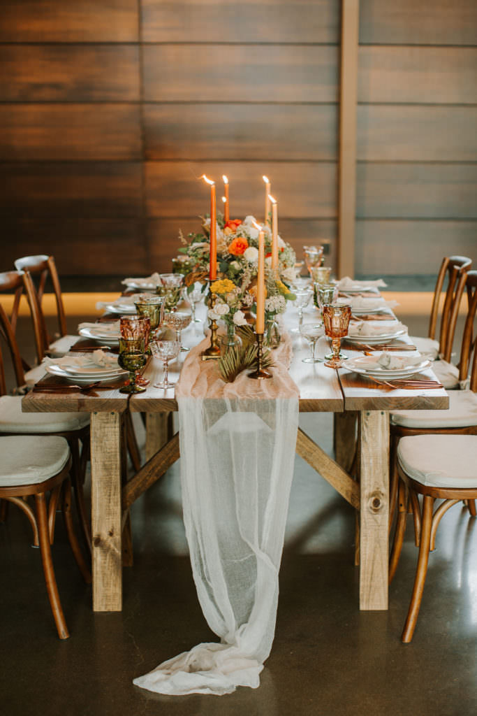 Boho styled wooden table with orange and peach colored candles, mixed florals, flatware, glasses and a tulle runner