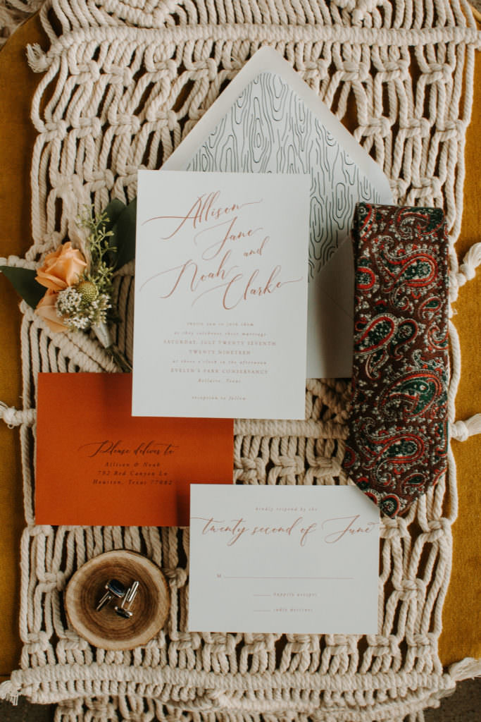 wedding invite flatlay with burnt orange envelope