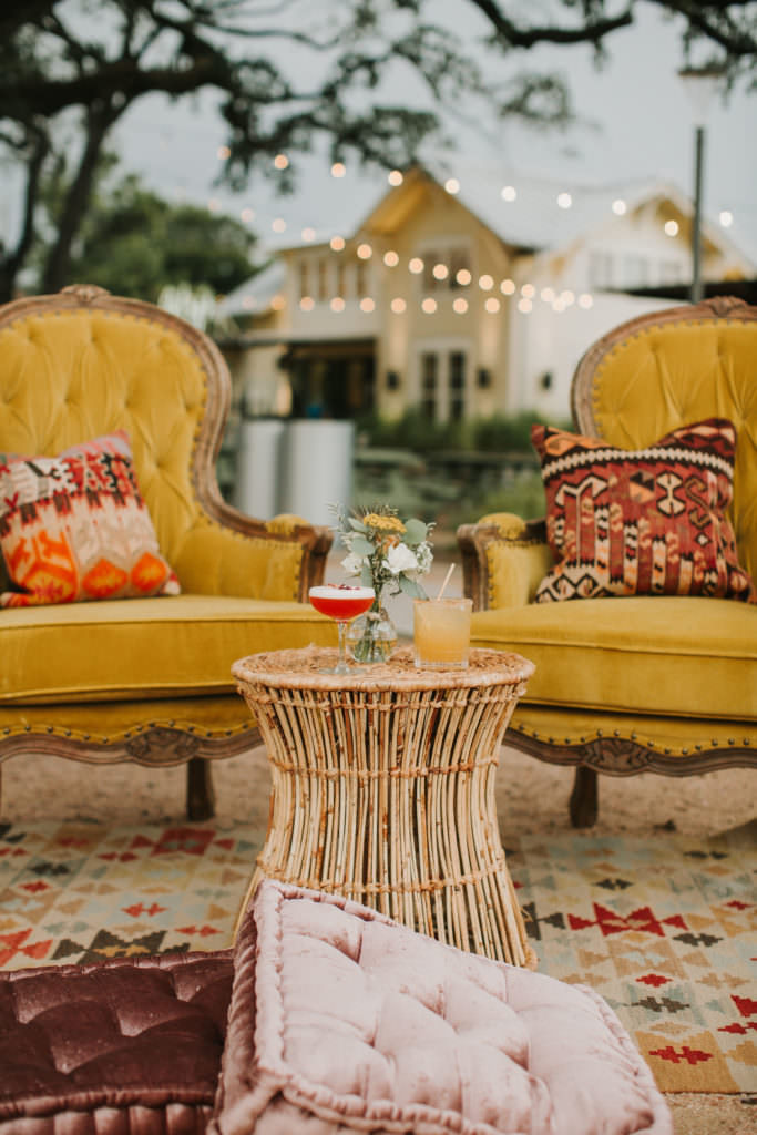 2 mustard colored chairs with cushions and cocktails sitting on a wicker style table