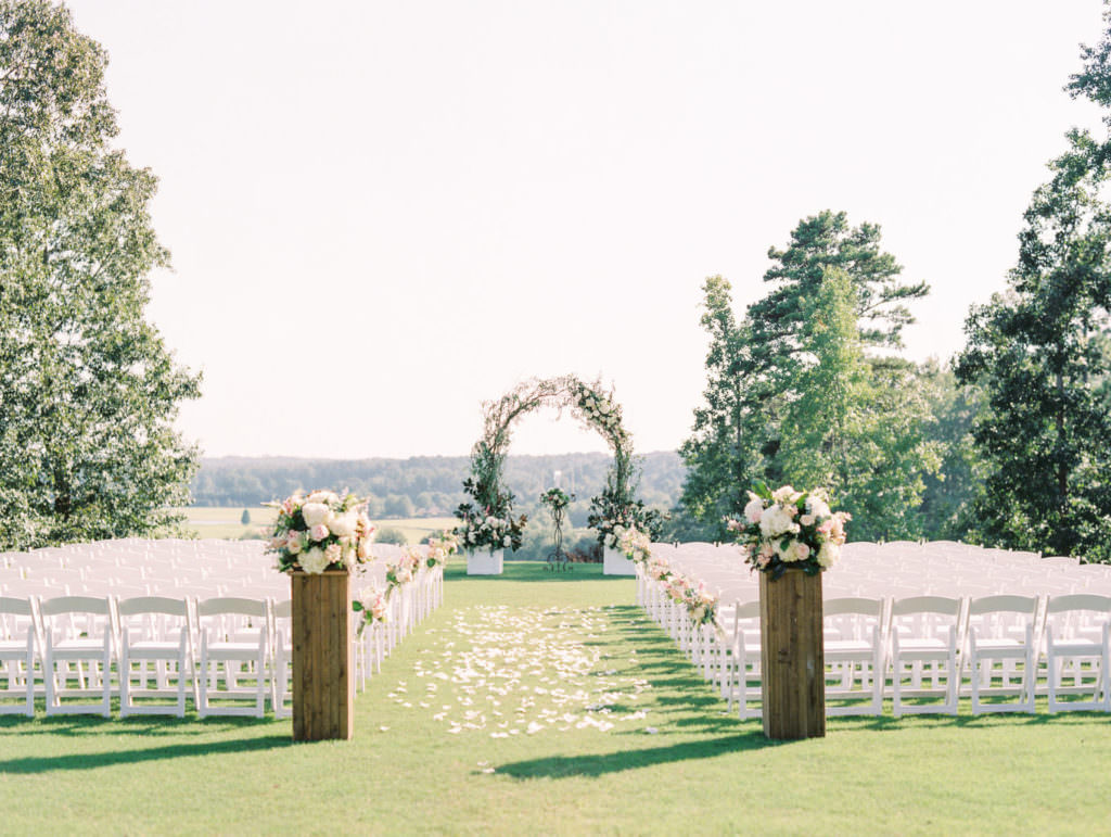 Outdoor wedding ceremony set up with circular arch, white seating and flower petals scattered