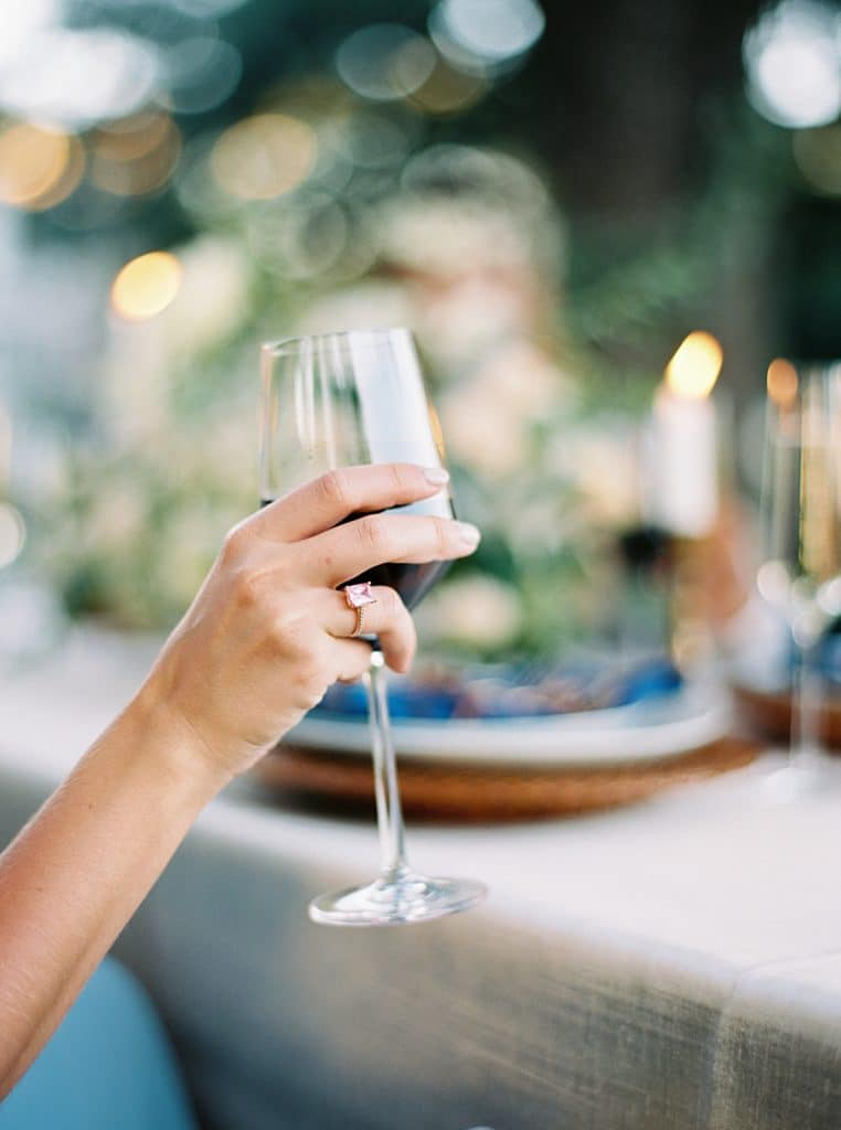 Glass of red wine being held at outdoor wedding reception