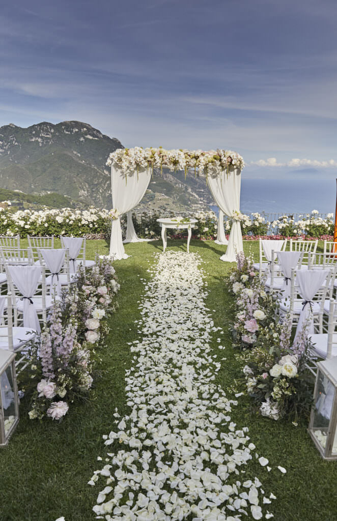Wedding ceremony set up, with rose petal aisle, chairs and florals and a wedding arch. How to get married in Europe.