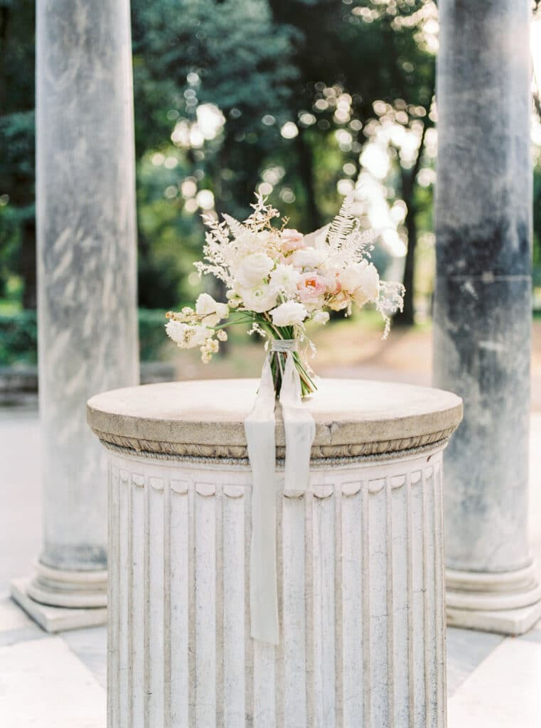 Bouquet of flowers send on a concrete pillar in Rome, Italy. How to get married in Europe.