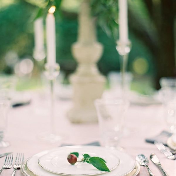 Wedding table set up with candles, elegant plates and silver flatware