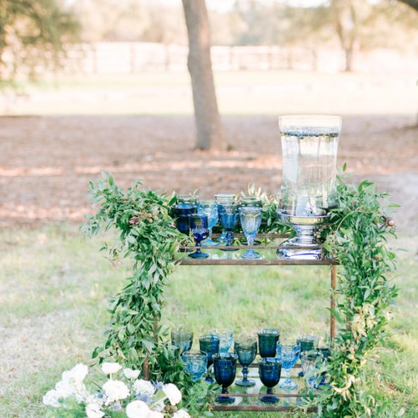 Wedding water station with pitcher and blue glasses on a stand with green foliage
